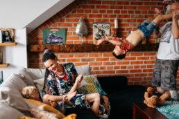 sesja rodzinna w domu z niezwykłą energią. Uśmiechnięci rodzice świetnie bawią się w swoim domu