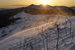 wschód słońca w Bieszczadach na połoninach okrytych śniegiem. Wiejący wiatr unosi śnieg oświetlając ciepłym światłem. Zdjęcie z Warsztatów fotograficznych Nowe spojrzenia