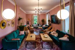 przepiękne wnętrze w stylu boho. zielone zamszowe sofy, plecione siedziska i dużo poduszek w pudrowo różowym wnętrzu hotelu Boho House w bieszczadach