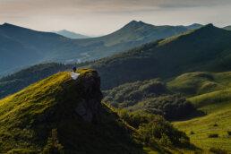 sesja w Bieszczadach soczyście zielone połoniny w Bieszczadach oświetlone ciepłym światłem w środku pełnego lata dwoje zakochanych ludzi pan młody i panna młoda zdobywają jeden ze szczytów a wiatr rozwiewa białą suknię wszystko wygląda jak obrazek rodem z J.R.R. Tolkiena zieleń szczyty lato widoki pejzaż