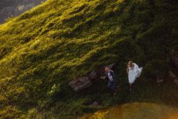 Panna młoda w Białej sukni całuje się z panem młodym w granatowym garniturze pan młody podskakuje na zielonych połoninach w blasku słońca