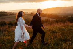 Biegnąca para młoda trzymająca się za ręce po łąkach w blasku zachodzącego słońca sesja. w Bieszczadach buty
