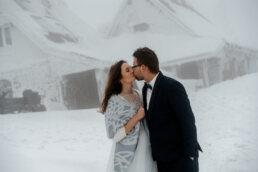 całująca się para młoda na szczycie połonin w zimie a w tle Chatka Puchatka