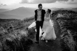 spacer po rozwianych połoninach w Bieszczadach para młoda spogląda na siebie z uśmiechem a w tle widać góry i lecące kruki