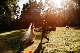 folklorystyczna sesja w Bieszczadach z owcami, para młoda biega w blasku zachodzącego słońca wśród pasących się owiec a w tle widnieje kolorowa cerkiwew
