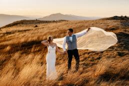sesja ślubna na połoninach złota trawa i wiatr powiewający welonem panny młodej