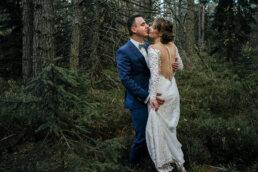 Panna młoda w Białej sukni całuje się z panem młodym w granatowym garniturze w zielonym lesie w Bieszczadach